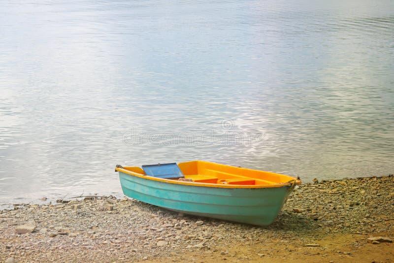 De kleine boot van kustnavigatie wordt vastgelegd Een kleine boot op de kust van het meer Rust op het water en de visserij Reddin royalty-vrije stock fotografie