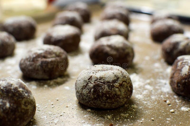 De kleine bruine die koekjes van de chocoladepeperkoek leggen op een bakselblad met gepoederde suiker wordt bestrooid royalty-vrije stock foto's