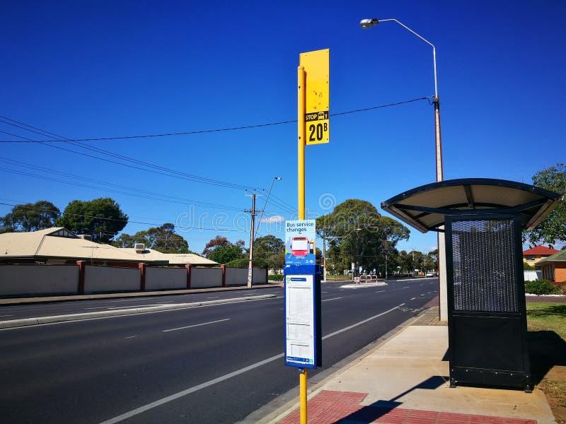 De Kleine bushalte in landelijke stad met blauwe hemeldag stock afbeelding
