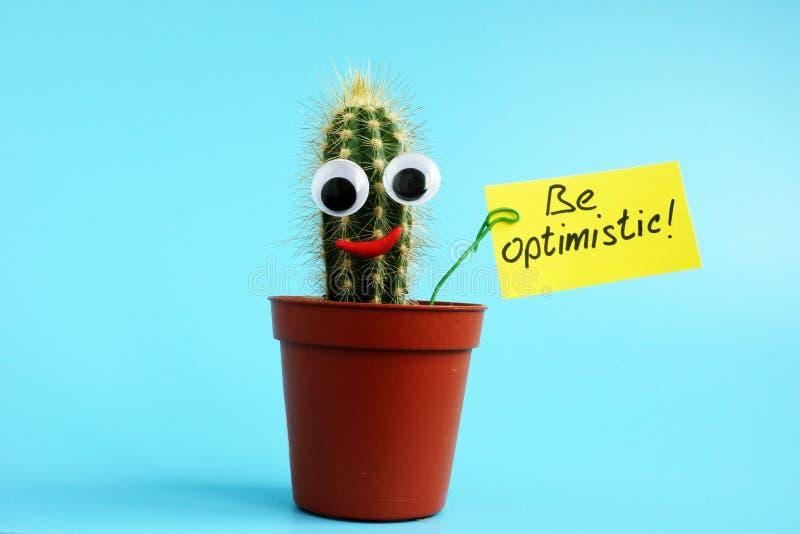 De kleine cactus houdt het teken optimistisch is royalty-vrije stock fotografie