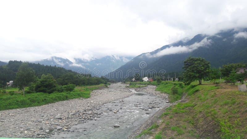 De kleine die rivier met de achtergrond van de berg met wolk wordt behandeld royalty-vrije stock afbeeldingen