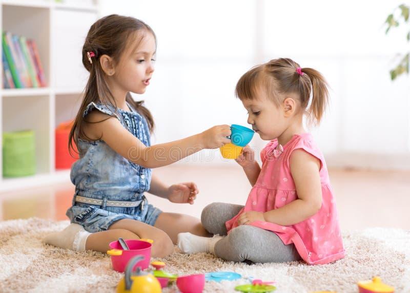 De kleine gelukkige kinderen, de leuke peuter en de jong geitjemeisjes spelen thuis met plastic stuk speelgoed keuken op vloer of royalty-vrije stock foto