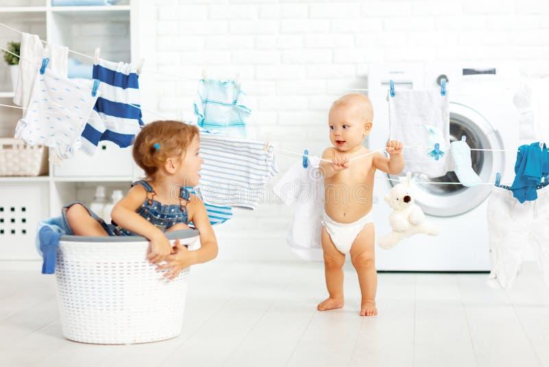 De kleine gelukkige zuster en de broer van helpers grappige jonge geitjes in wasserij aan royalty-vrije stock foto