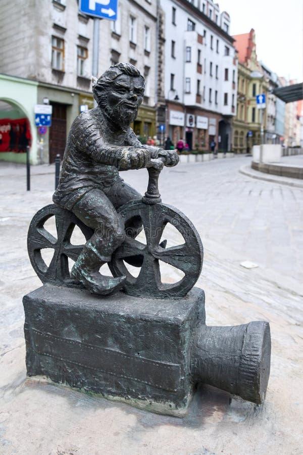 De kleine gnoom van het bronsstandbeeld door naam - Kinoman Mlodszy, gnoom-movieman zitting op de filmprojector stock foto