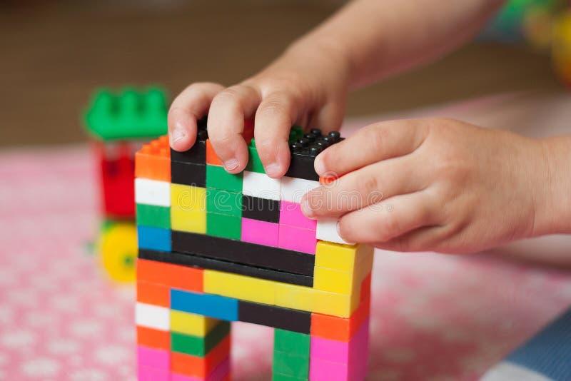 De kleine handen van het kind verzamelt de heldere plastiek gekleurde Ontwerper Onderwijsspeelgoed en vroeg het leren stock foto