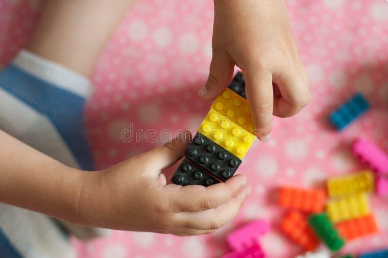 De kleine handen van het kind verzamelt de heldere plastiek gekleurde Ontwerper Onderwijsspeelgoed en vroeg het leren royalty-vrije stock afbeeldingen