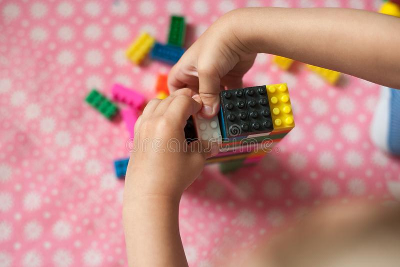 De kleine handen van het kind verzamelt de heldere plastiek gekleurde Ontwerper Onderwijsspeelgoed en vroeg het leren royalty-vrije stock foto
