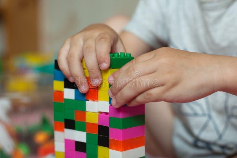 De kleine handen van het kind verzamelt de heldere plastiek gekleurde Ontwerper Onderwijsspeelgoed en vroeg het leren royalty-vrije stock foto's