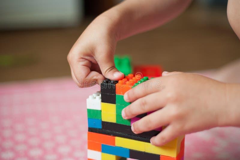 De kleine handen van het kind verzamelt de heldere plastiek gekleurde Ontwerper Onderwijsspeelgoed en vroeg het leren stock afbeelding
