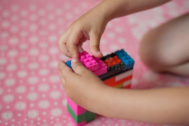 De kleine handen van het kind verzamelt de heldere plastiek gekleurde Ontwerper Onderwijsspeelgoed en vroeg het leren stock afbeeldingen