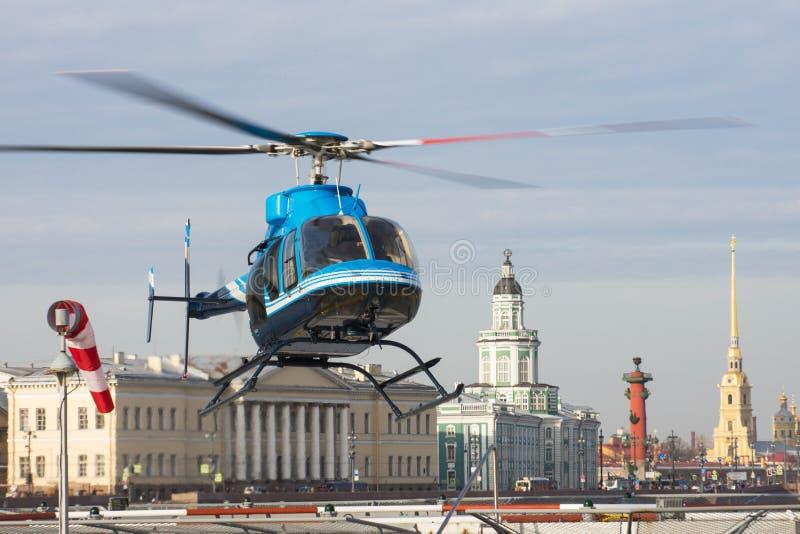 De kleine helikopter stijgt van de helihaven in St. Petersburg, tegen de achtergrond van Kunstkamera, de pijl van Vasilyevs op stock foto