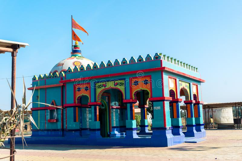 De kleine Hindoese tempel met gravures in levendige blauw en rood schoot in Gujarat India royalty-vrije stock foto's