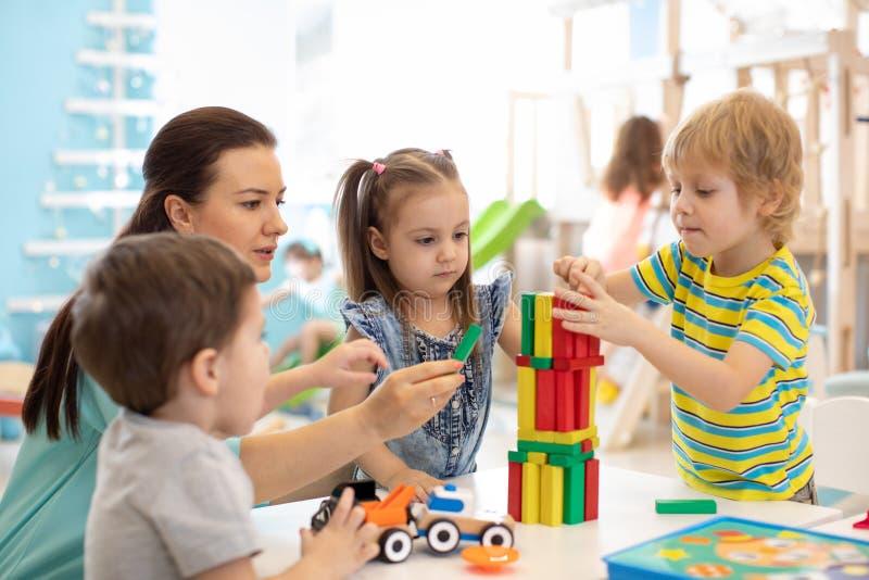 De kleine jonge geitjes bouwen thuis blokspeelgoed of opvang Jonge geitjes die met kleurenblokken spelen Onderwijsspeelgoed voor  stock afbeeldingen