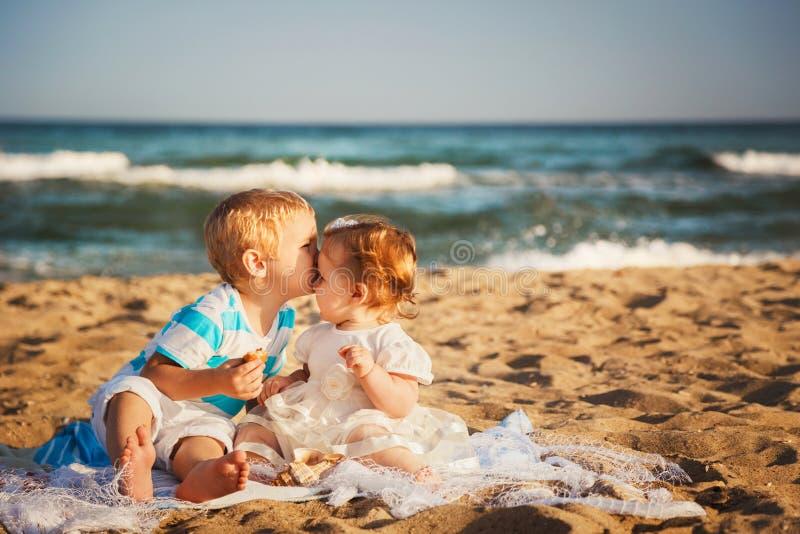 De kleine jonge geitjes kussen en hebben samen pret bij strand dichtbij het oceaan, gelukkige concept van de levensstijlfamilie stock afbeeldingen