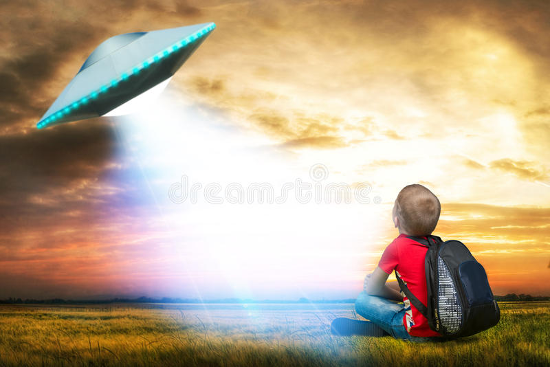 De kleine jongen bekijkt omhoog een niet geïdentificeerd vliegend voorwerp dat in de hemel verscheen royalty-vrije stock foto's