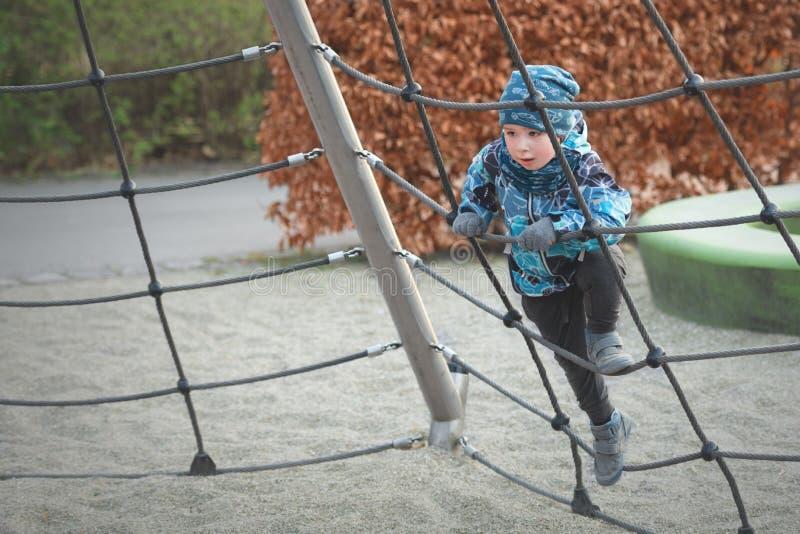 De kleine jongen beklimt de touwladder bij speelplaats in de lente stock afbeeldingen