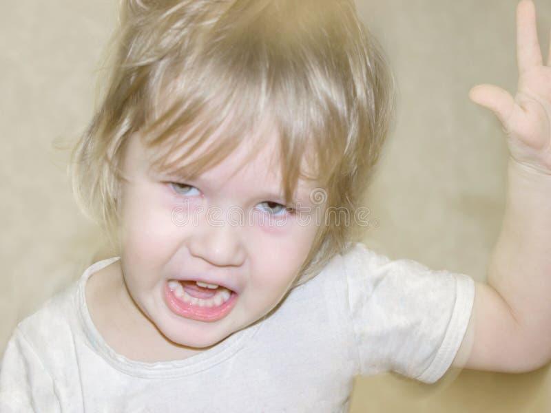 De kleine jongen is boos, boos, gillen, die proberen te raken stock foto