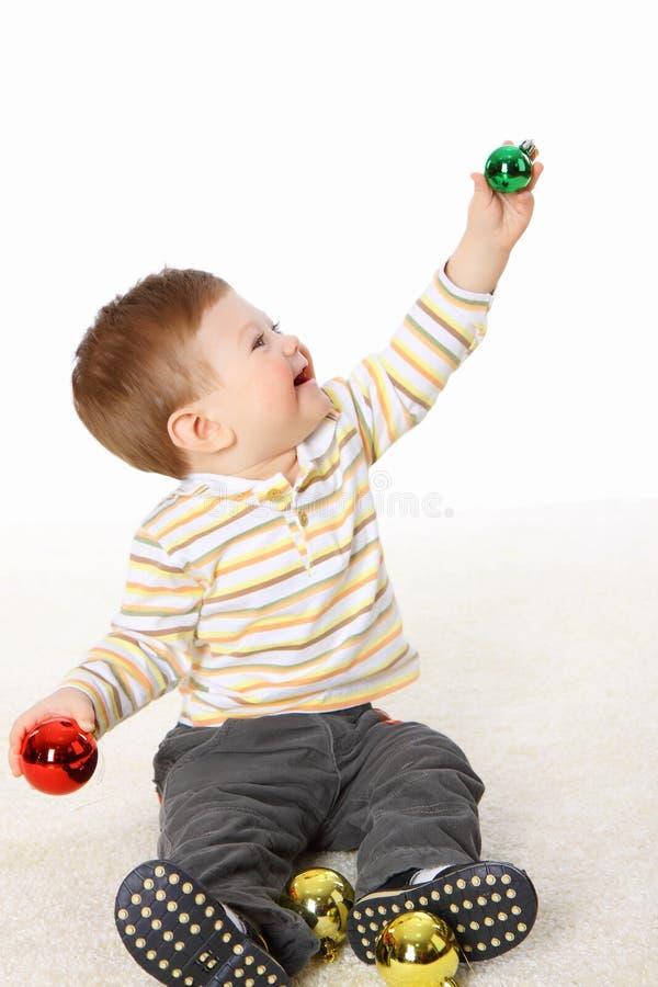 De kleine jongen die met het speelgoed van het Nieuwjaar speelt stock afbeelding