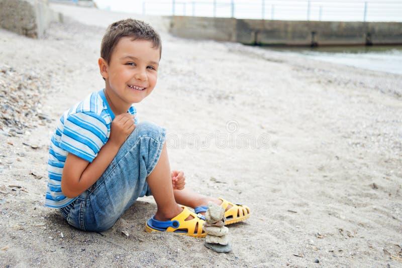 de kleine jongen door het overzees verzamelt zeeschelpen op het strand Zonsondergang Gelukkige kinderjaren de zomervakantie op ze stock fotografie