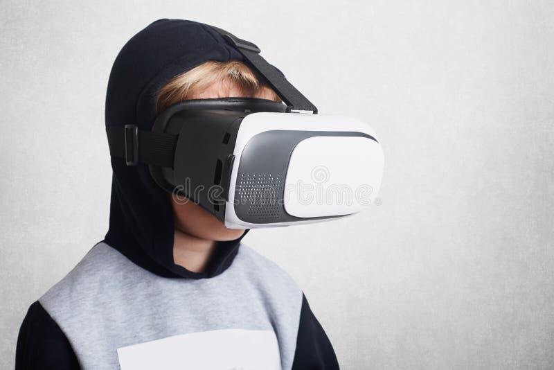 De kleine jongen draagt virtuele werkelijkheidsglazen, ziet verbaasd iets, stelt tegen witte achtergrond Kinderen, moderne techno royalty-vrije stock afbeelding