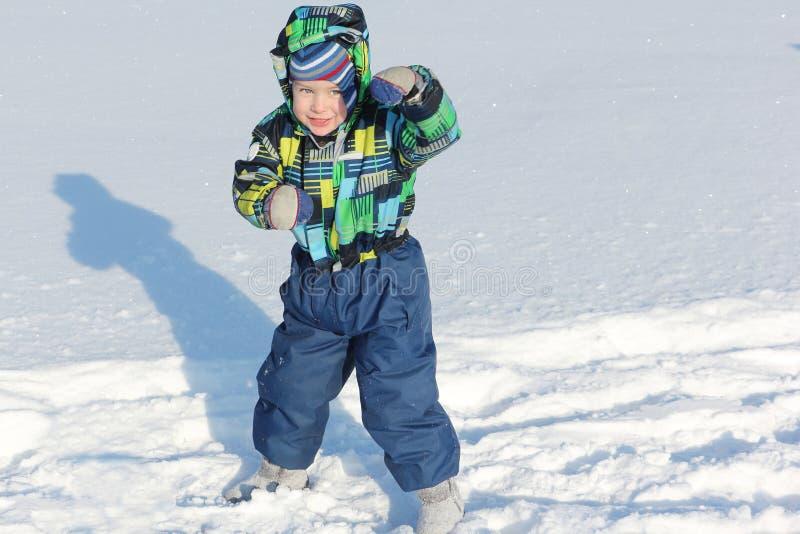 De kleine jongen in een kleurenjasje die zich in een strijdlustig rek bevinden stock foto