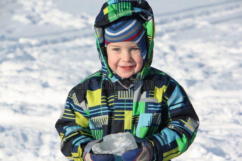 De kleine jongen in een kleurenjasje het stuk van ter beschikking het iceholding stock foto