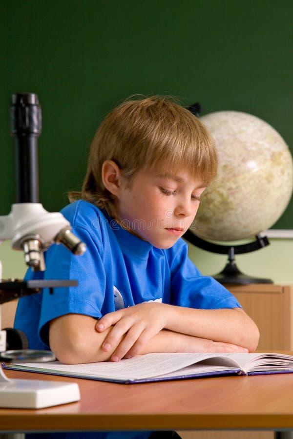 De kleine jongen is geconcentreerd met lezing royalty-vrije stock afbeeldingen