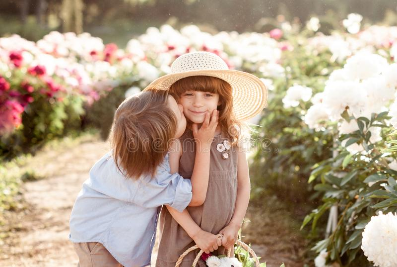 De kleine jongen kust het mooie meisje in een strohoed in de tuin van pioenen royalty-vrije stock fotografie