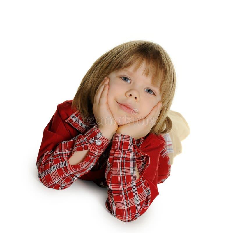 De kleine jongen legt op een vloer stock afbeelding