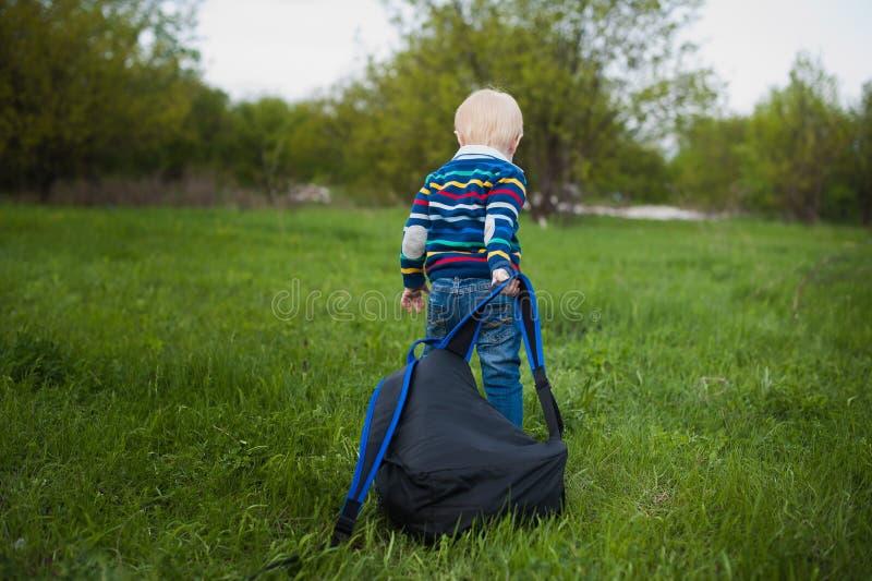 De kleine jongen met blond haar die een grote rugzakchery op het groene gras in aard, reis, baby, avontuur trekken royalty-vrije stock foto
