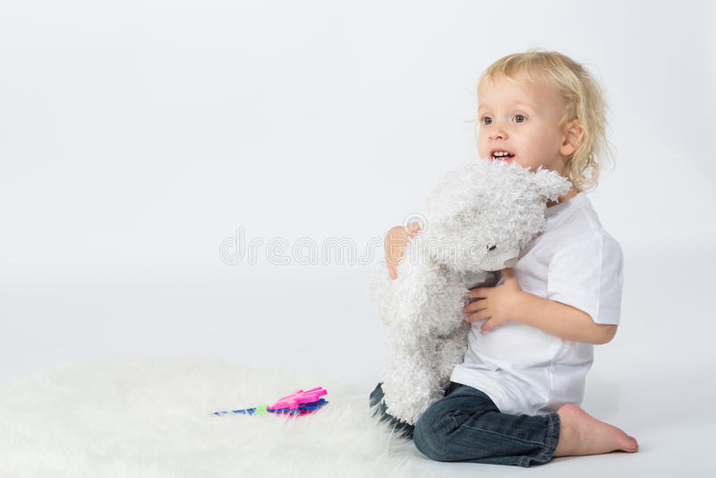 De kleine jongen met een beer in zijn handen het spelen royalty-vrije stock fotografie