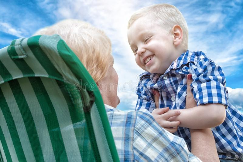 De kleine jongen omhelst teder zijn geliefde grootmoeder Liefdegeneraties stock foto's