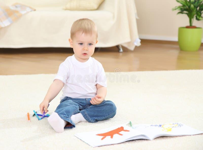 De kleine jongen op een vloer royalty-vrije stock foto