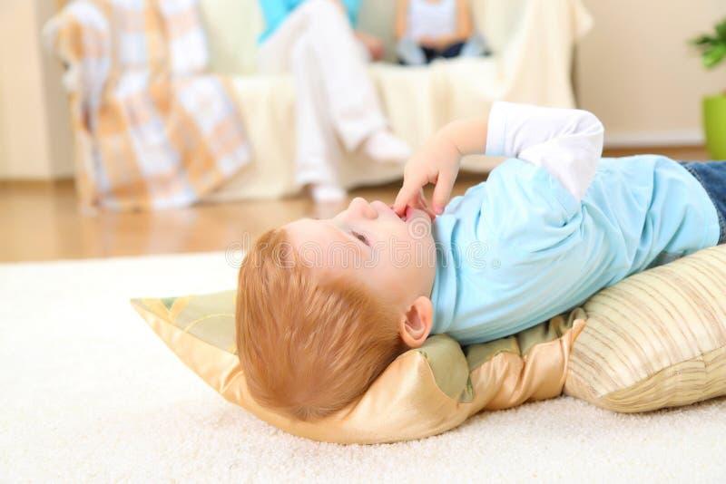 De kleine jongen op een vloer royalty-vrije stock afbeelding