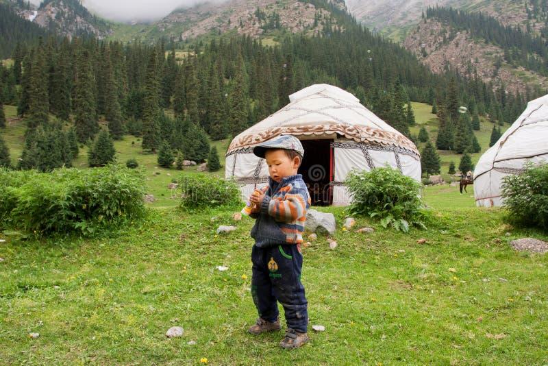 De kleine jongen speelt dichtbij landbouwershuis Yurt in een vallei tussen de bergen van Centraal-Azië stock afbeeldingen