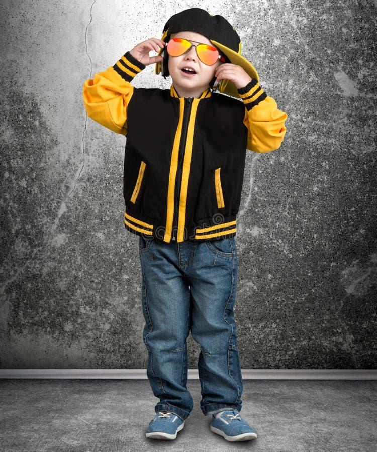 De kleine jongen in de stijl van Hiphop Kinderen` s manier GLB en jasje Jonge Rapper Koel DJ stock foto