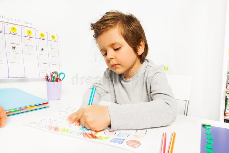 De kleine jongen trekt met potlood op de document zitting stock fotografie