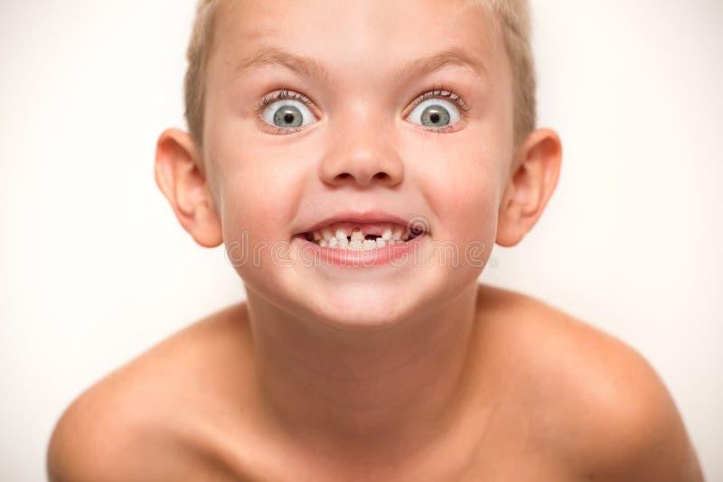 De kleine jongen valt een melktand uit Het kind wacht op de tandfee stock foto