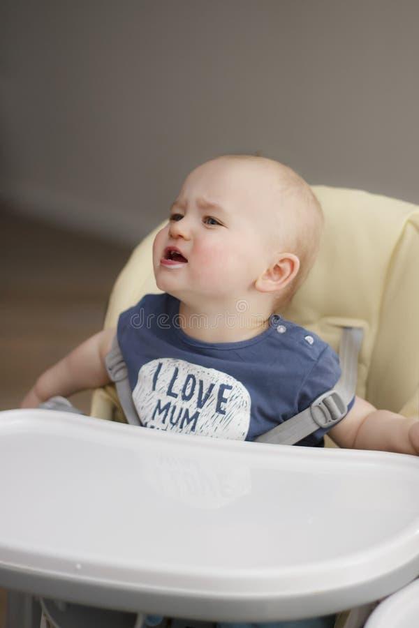 De kleine jongen wil niet eten en schreeuwt stock afbeelding
