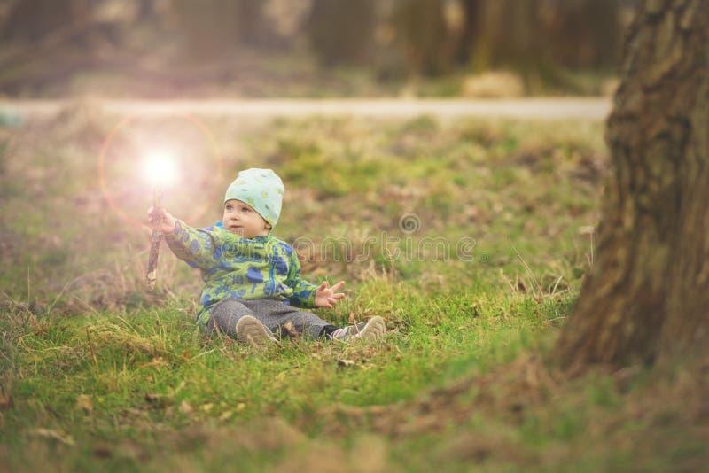 De kleine jongen zit op gras en behandelingstoverstokje in de lentepark dichtbij grote boom royalty-vrije stock foto