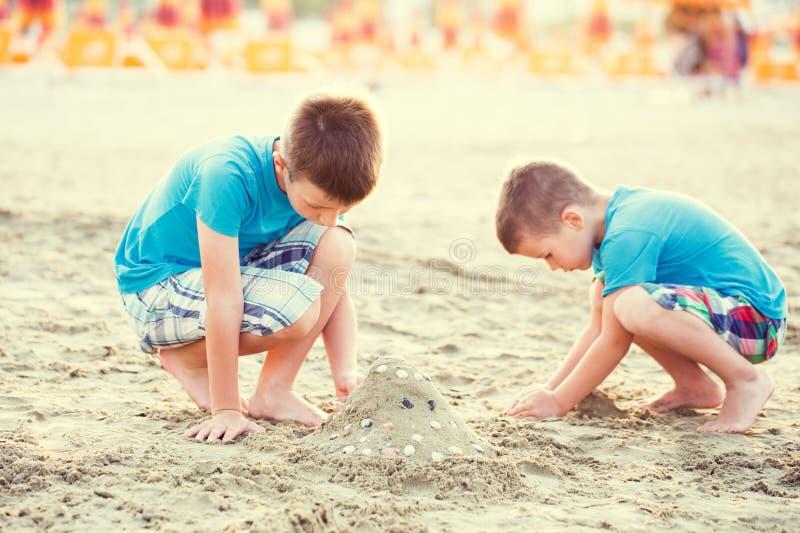 De kleine jongens bouwen zandvesting royalty-vrije stock afbeelding