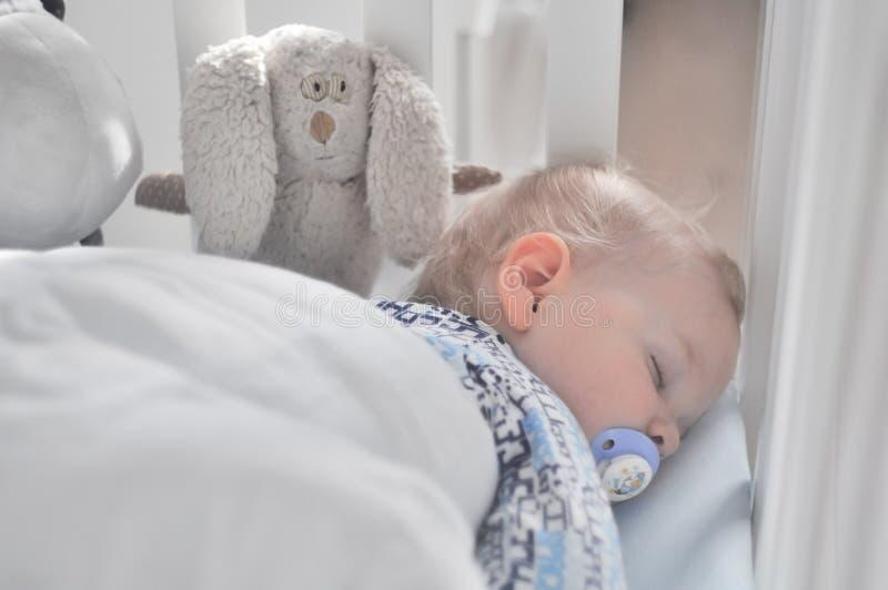 De kleine jongensslaap met een fopspeen stock fotografie