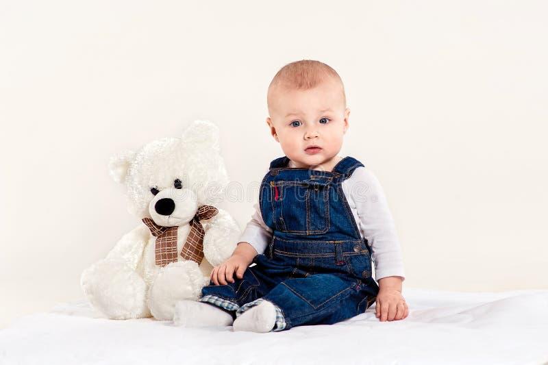 De kleine jongensspelen met een teddybeer stock afbeelding
