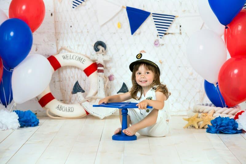 De kleine kapitein zit op de vloer in een mariene stijl Wij merken het eerste jaar stock foto