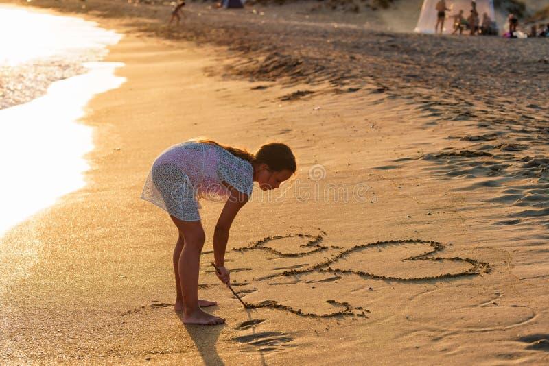 De kleine Kaukasische cijfers van de meisjestekening van harten met een stok op zandig strand bij de zomerzonsondergang stock foto