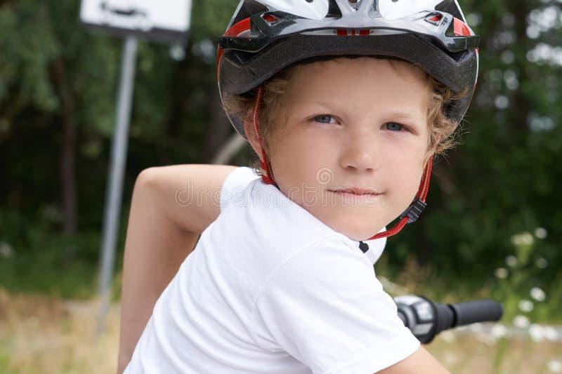 De kleine Kaukasische jongen in beschermende helm bevindt zich leunend op fiets het stellen voor de camera Tiener klaar te berijd stock fotografie