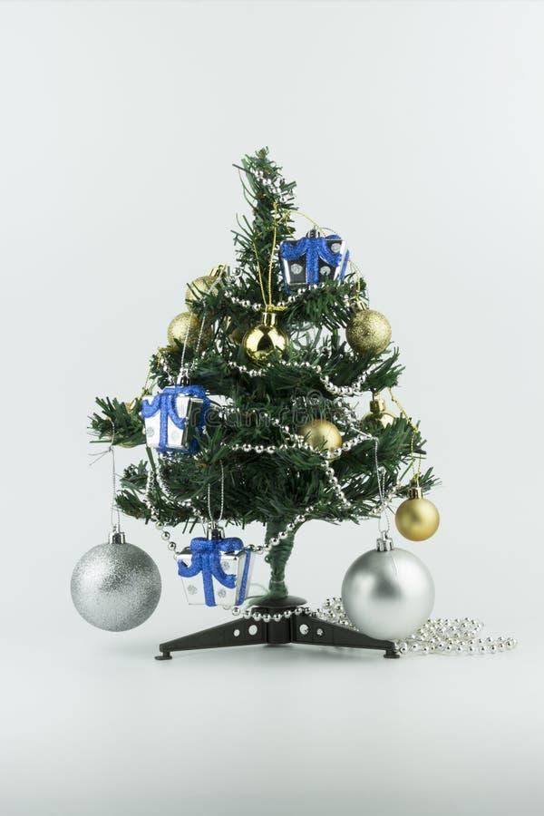 De kleine Kerstboom is verfraaid die met ornamenten zoals bal en gift, op witte achtergrond wordt geïsoleerd stock foto