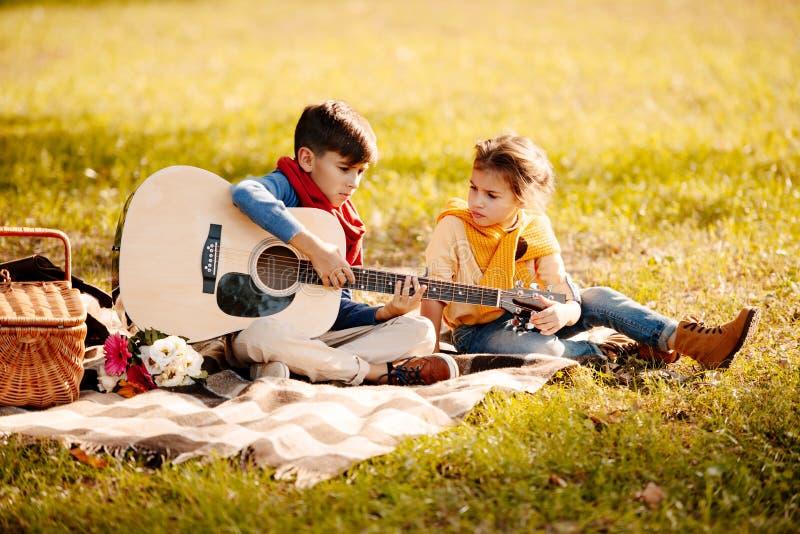 De kleine kinderen die op een picknick zitten bedekken in een park met akoestisch royalty-vrije stock afbeeldingen