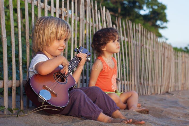 De kleine kinderen hebben pret op zonsondergang tropisch strand stock foto