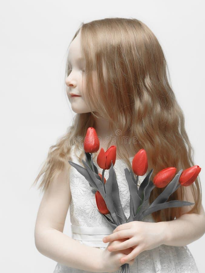 De kleine kinderen houden van mooie tulpen stock afbeeldingen
